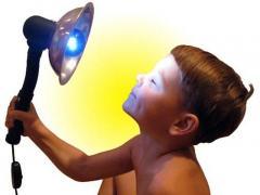 Ребенок греет нос синей лампой